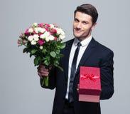 Homem de negócios que guarda flores e caixa de presente Imagem de Stock Royalty Free