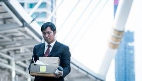 Homem de negócios que guarda guardar a caixa de cartão com os pertences pessoais que saem do trabalho despedido Foto de Stock Royalty Free