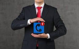 Homem de negócios que guarda o ícone Fotos de Stock
