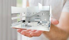 Homem de negócios que guarda o apartamento branco da rendição 3D em sua mão Imagem de Stock Royalty Free