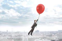 Homem de negócios que guarda o balão e o voo Imagem de Stock