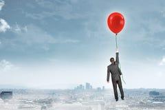 Homem de negócios que guarda o balão e o voo Fotos de Stock Royalty Free