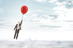 Homem de negócios que guarda o balão e o voo Fotografia de Stock Royalty Free