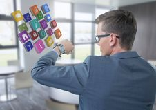 Homem de negócios que guarda o braço com ícones do relógio e dos apps aos olhos no escritório Imagem de Stock
