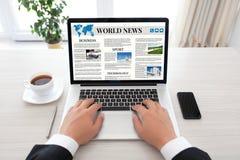 Homem de negócios que guarda o caderno com o local das notícias do mundo na tela Fotografia de Stock