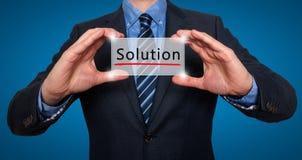 Homem de negócios que guarda o cartão branco com sinal da solução, azul - estoque Imagens de Stock