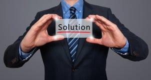 Homem de negócios que guarda o cartão branco com sinal da solução, cinza - estoque Imagens de Stock Royalty Free