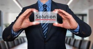Homem de negócios que guarda o cartão branco com sinal da solução, escritório - Stoc Fotos de Stock Royalty Free