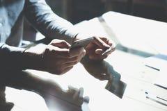 Homem de negócios que guarda o cartão de crédito da mão e que usa o smartphone Cartão em linha do plástico dos pagamentos modelo  Foto de Stock