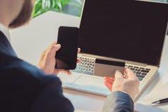 Homem de negócios que guarda o cartão de crédito e o smartphone ao sentar-se no local de trabalho Imagens de Stock