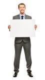 Homem de negócios que guarda o cartaz branco vazio que mostra o espaço da cópia imagens de stock royalty free