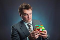 Homem de negócios que guarda o cubo do rubik em suas mãos foto de stock royalty free