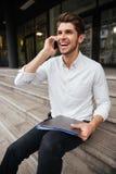 Homem de negócios que guarda o dobrador com originais e que fala no telefone celular Imagens de Stock