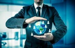Homem de negócios que guarda o globo em suas mãos O conceito da gestão do pessoal em todo o mundo Fotografia de Stock Royalty Free