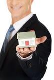 Homem de negócios que guarda o modelo da casa Imagem de Stock Royalty Free