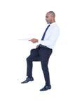 Homem de negócios que guarda o papel e a mala de viagem Fotografia de Stock Royalty Free