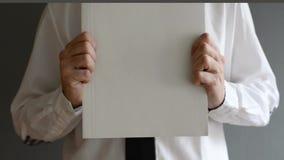 Homem de negócios que guarda o papel vazio com espaço da cópia filme