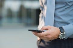 Homem de negócios que guarda o smartphone Imagens de Stock Royalty Free