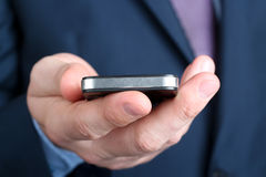 Homem de negócios que guarda o telefone celular Imagens de Stock