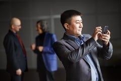 Homem de negócios que guarda o telefone esperto móvel usando o app Foto de Stock