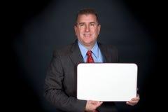 Homem de negócios que guarda o whiteboard imagem de stock