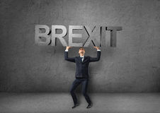 Homem de negócios que guarda a palavra pesada 'do brexit 3d' sobre sua cabeça Fotos de Stock