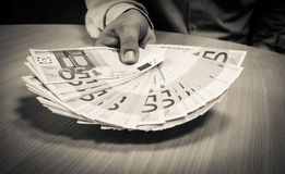 Homem de negócios que guarda para fora cinqüênta contas do Euro sobre uma mesa imagens de stock royalty free