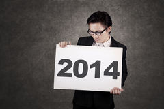 Homem de negócios que guarda a placa o ano novo 2014 Imagem de Stock
