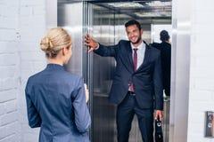 Homem de negócios que guarda a porta do elevador para a mulher fotografia de stock