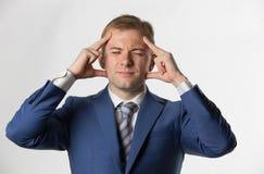 Homem de negócios que guarda principal com uma dor de cabeça fotografia de stock royalty free