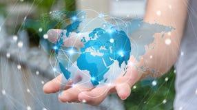 Homem de negócios que guarda a rede global na rendição da terra 3D do planeta Fotos de Stock Royalty Free