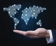 Homem de negócios que guarda símbolos dos povos com mapa do mundo Busin global imagens de stock royalty free