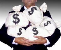 HOMEM DE NEGÓCIOS QUE GUARDA SACOS DO DINHEIRO imagem de stock royalty free