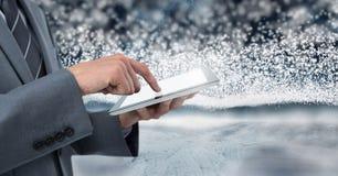Homem de negócios que guarda a tabuleta com backgorund da neve Imagem de Stock