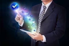 Homem de negócios que guarda a tabuleta com pressão do botão do ícone da marca de verificação fotografia de stock