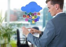Homem de negócios que guarda a tabuleta de vidro com ícones dos apps no escritório brilhante Fotografia de Stock Royalty Free