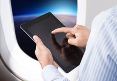 Homem de negócios que guarda a tabuleta digital no avião Imagem de Stock