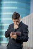 Homem de negócios que guarda a tabuleta digital que está fora de trabalho fora o distrito financeiro Fotografia de Stock