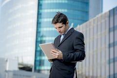 Homem de negócios que guarda a tabuleta digital que está o distrito financeiro fora de trabalho Fotografia de Stock