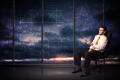 Homem de negócios que guarda a tabuleta na sala do escritório com cartas do gráfico em w Imagem de Stock
