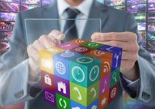 Homem de negócios que guarda a tela de vidro com apps com visuals coloridos das telas foto de stock