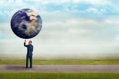 Homem de negócios que guarda a terra do planeta com um dedo Fotos de Stock