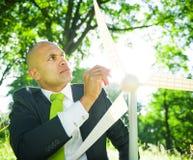 Homem de negócios que guarda a turbina eólica nas madeiras Fotos de Stock Royalty Free