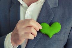 Homem de negócios que guarda um coração verde fotos de stock royalty free