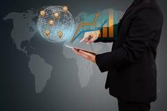 Homem de negócios que guarda um gráfico de negócio da exibição da tabuleta em s virtual Fotos de Stock