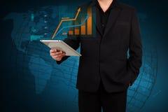 Homem de negócios que guarda um gráfico de negócio da exibição da tabuleta em s virtual Foto de Stock Royalty Free