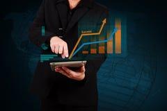 Homem de negócios que guarda um gráfico e um globo de negócio da exibição da tabuleta sobre Imagens de Stock Royalty Free