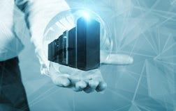 Homem de negócios que guarda um holograma com os super-computadores dentro do conceito de dados grandes Foto de Stock