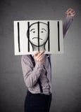 Homem de negócios que guarda um papel com um prisioneiro atrás das barras sobre mim fotografia de stock