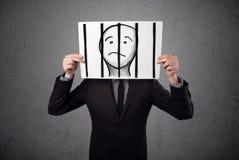 Homem de negócios que guarda um papel com um prisioneiro atrás das barras sobre mim imagem de stock